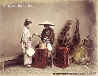 明治時代中期に撮影された甘酒売り。釜のなかに甘酒が入っており、右側の箱には茶碗などが収納されています